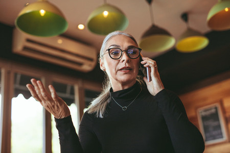 Mature woman talking on mobile phone at cafe