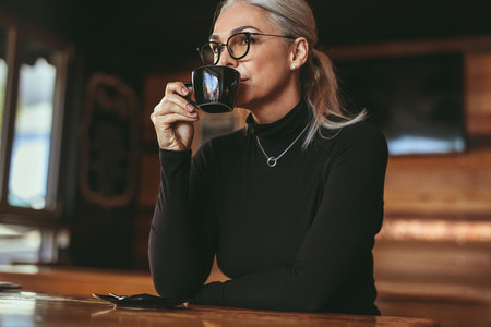 Thoughtful senior woman sitting at cafe drinking coffee