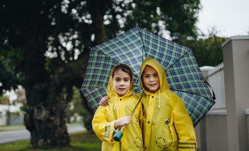 Beautiful sisters under an umbrella outdoors