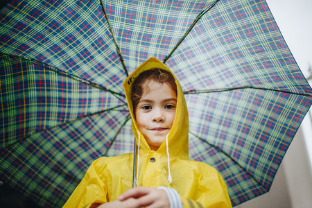 Cute little girl in raincoat with umbrella