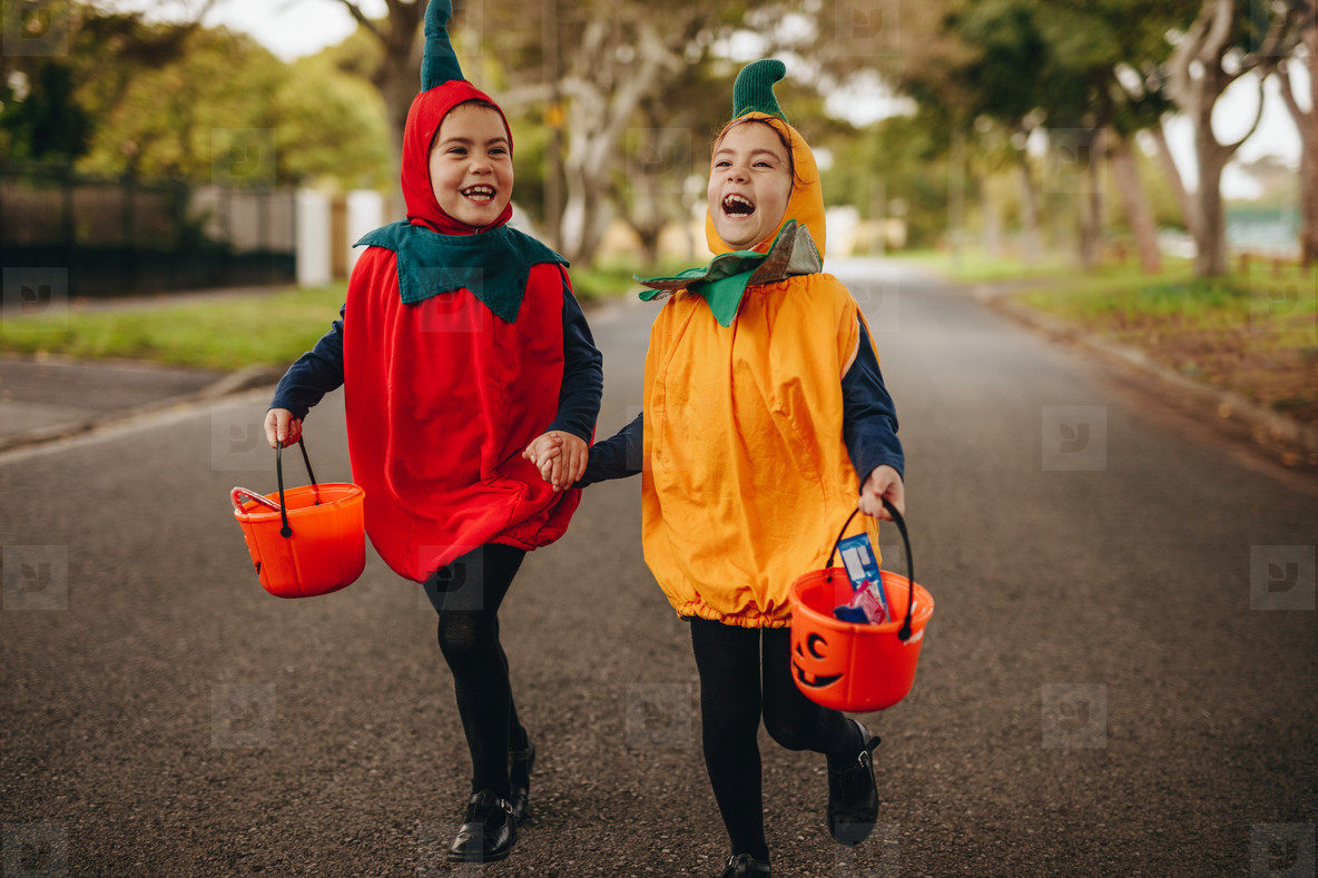 twin girls in halloween costume out the road