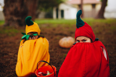 Twin sisters tricking outdoors on halloween
