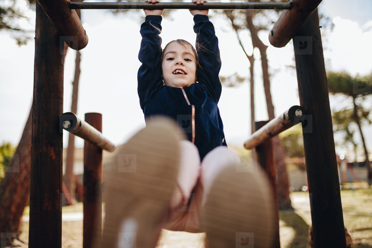 Cute little girl swinging on a metal frame