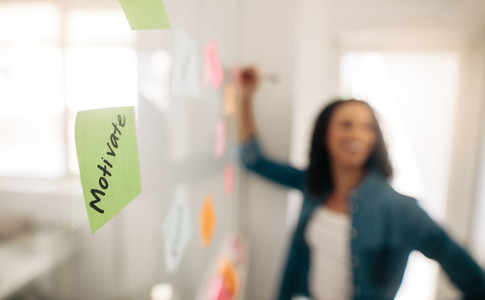 Sticky note with motivate written on it pasted on glass wall
