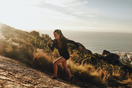 Fit woman running up a rocky mountain trail