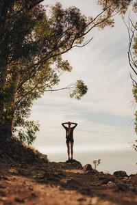 Female runner relaxing on mountain peak