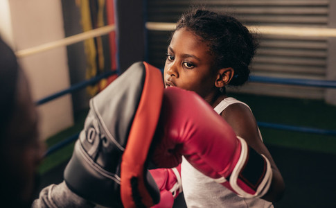 Boxing kid practicing punches on a punching pad