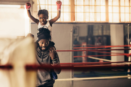 Trainer carrying a boxer kid on his shoulders in the gym