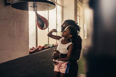 Coach training a kid on speedball punching