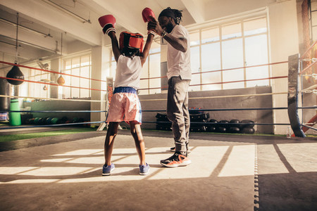 Coach raising the hand of a boxing kid in appreciation