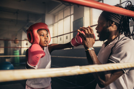 Boxing kid practicing punches with his coach