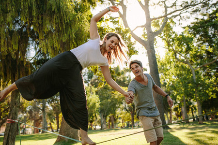 Woman practices slacklining in a park