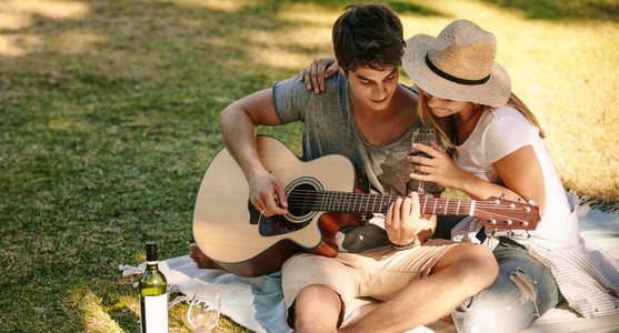 Man sitting in park with his girlfriend playing guitar