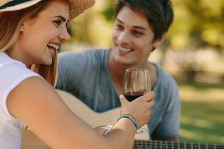 Romantic couple sitting in park drinking wine and playing guitar