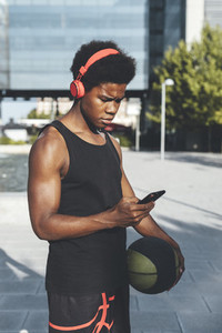 Young afro man chatting by phone listening music with red headphones and a basket ball in urban scenery