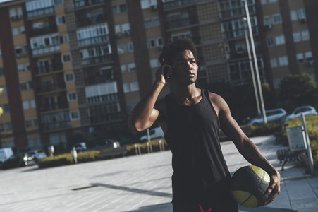 Portrait of young afro man listening music with red headphones and a basket ball in urban scenery