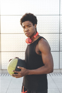 Portrait of young black man in urban scenery at sunset with red headphones and a basket ball