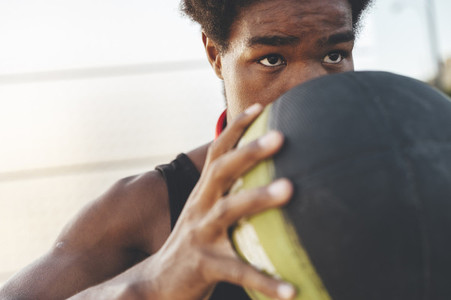 Close up of young black man with strong looking playing basketball