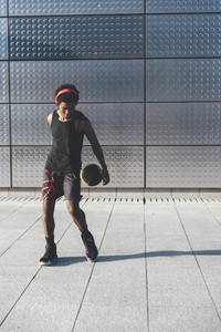 Handsome young afro american basketball player bouncing basket ball training in the city with red headphones