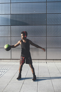 Handsome young afro american basketball player playing with basketball in urban scenery at sunset