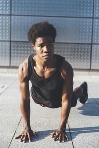 Front view of handsome young black basketball player doing chest press in urban scenery at sunset