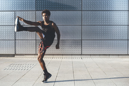 Side view of handsome young black basketball player warming up stretching legs in urban scenery at sunset