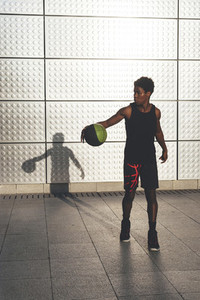 Young afro american basketball player bouncing basket ball training in the city with long shadow reflected on the wall