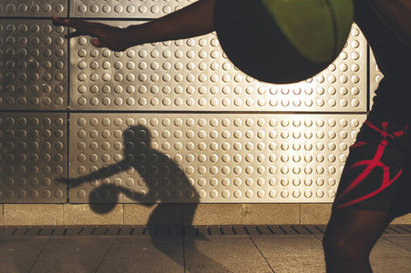 Silhouette of young afro american basketball player bouncing basket ball training in the city with long shadow reflected on the wall