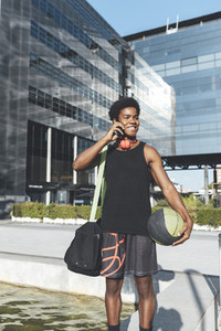 Young afro man talking by phone red headphones a basket ball and a bag waiting friends in urban scenery