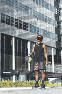 Young afro man bouncing basket ball listening music with red headphones in urban scenery