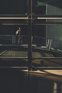 Young black man waiting friends carrying a basket ball framed in urban scenery