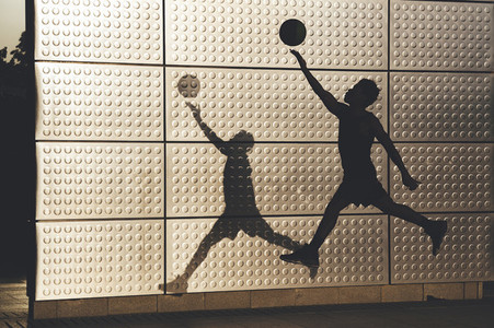 Young afro american basketball player jumping with basket ball training in the city with long shadow reflected on the wall