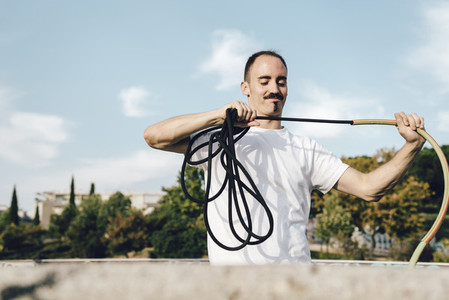 Aerial dancer handling ropes for safety in urban scenery
