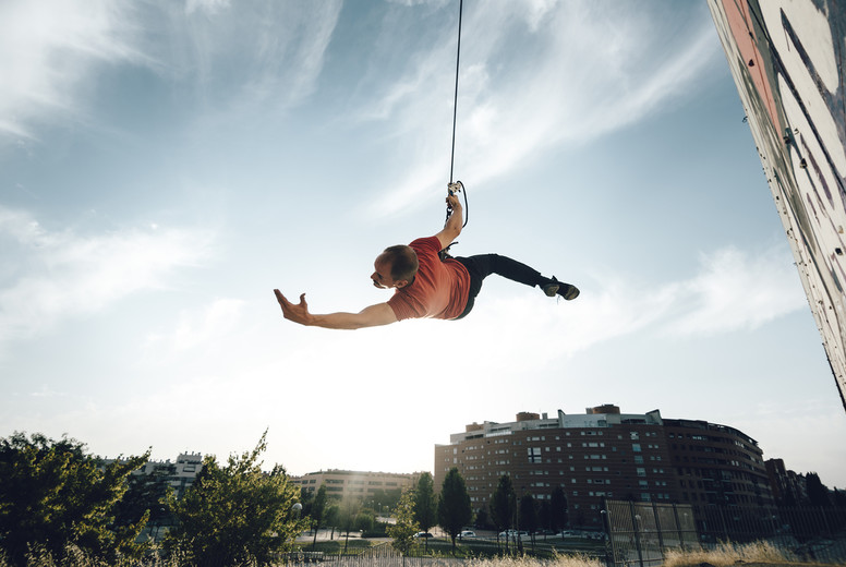 Dancer performing aerial dance hanging on harness on urban scenery at sunset