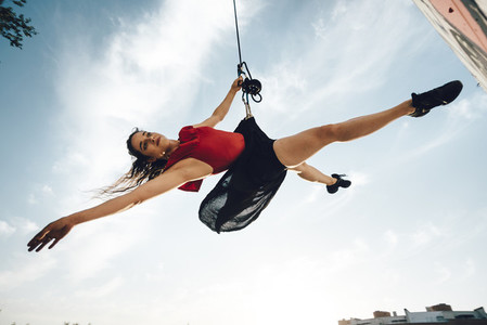 Sexy dancer performing aerial dance hanging on harness on urban scenery at sunset against blue sky