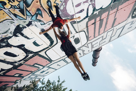 Couple of aerial dancers performing a choreography on urban scenery at sunset against graffitti wall
