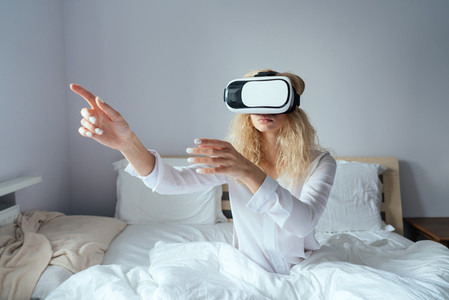 Girl sitting on a bed with VR headset