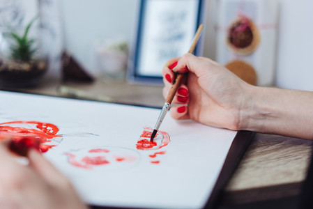 Young woman painting with watercolor paints