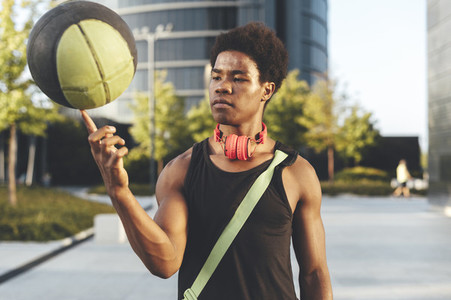 Young afro man rolling a basket ball wearing red headphones and a bag waiting friends in urban scenery