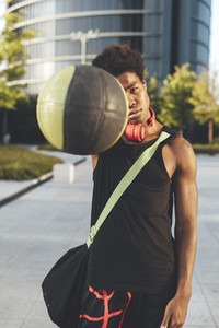 Portrait of young afro man with a basket ball  wearing red headphones and a bag waiting friends in urban scenery
