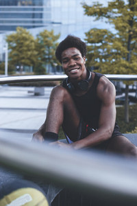 Young smiling afro man lacing baskeball shoes seated in urban scenery at dusk