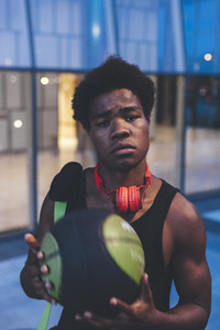 Portrait of young afro man with a basket ball wearing red headphones and a bag waiting friends in urban scenery at dusk