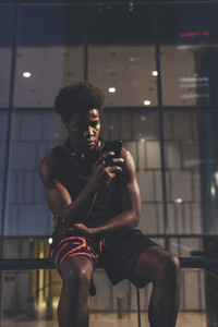 Young confident afro man talking by phone wearing sportswear in urban scenery at dusk
