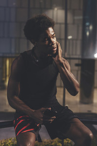 Portrait of young confident afro man holding phone wearing sportswear in urban scenery at dusk
