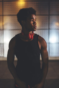 Portrait of young afro man wearing sportswear and red headphones in urban scenery at night with city lights