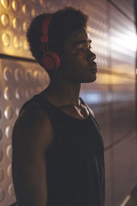 Portrait of young afro man listening music with red headphones  wearing sportswear in urban scenery at night with city lights