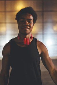 Portrait of  young confident afro man wearing red headphones in urban scenery at  night with city lights