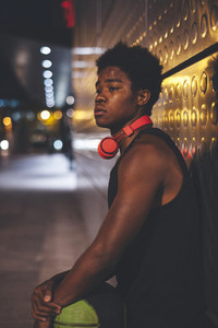 Portrait of young afro man with a basket ball wearing red headphones and a bag waiting friends in urban scenery at night with city lights