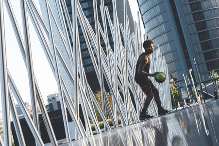 Young afro american basketball player bouncing basket ball training in the city surrounded by architectural space