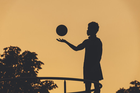 Silhouette of young afro american basketball player playing with a basket ball in urban scenery at sunset